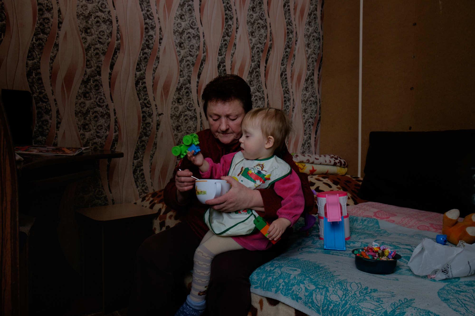Валентина Кришталева присматривает за младшей внучкой. Валентина и дочь вместе со своей семьей живут в общежитии при гомельском речном порту.